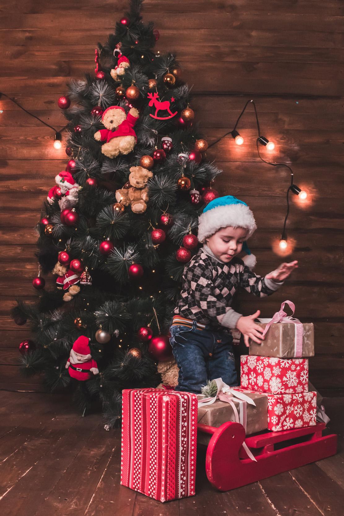 ребёнок возле ёлки складывает игрушки на сани, новогодняя детская фотосессия в студии, фото ребенка в фотостудии, мальчик в шапке деда мороза, детский фотограф в фотостудию Киев