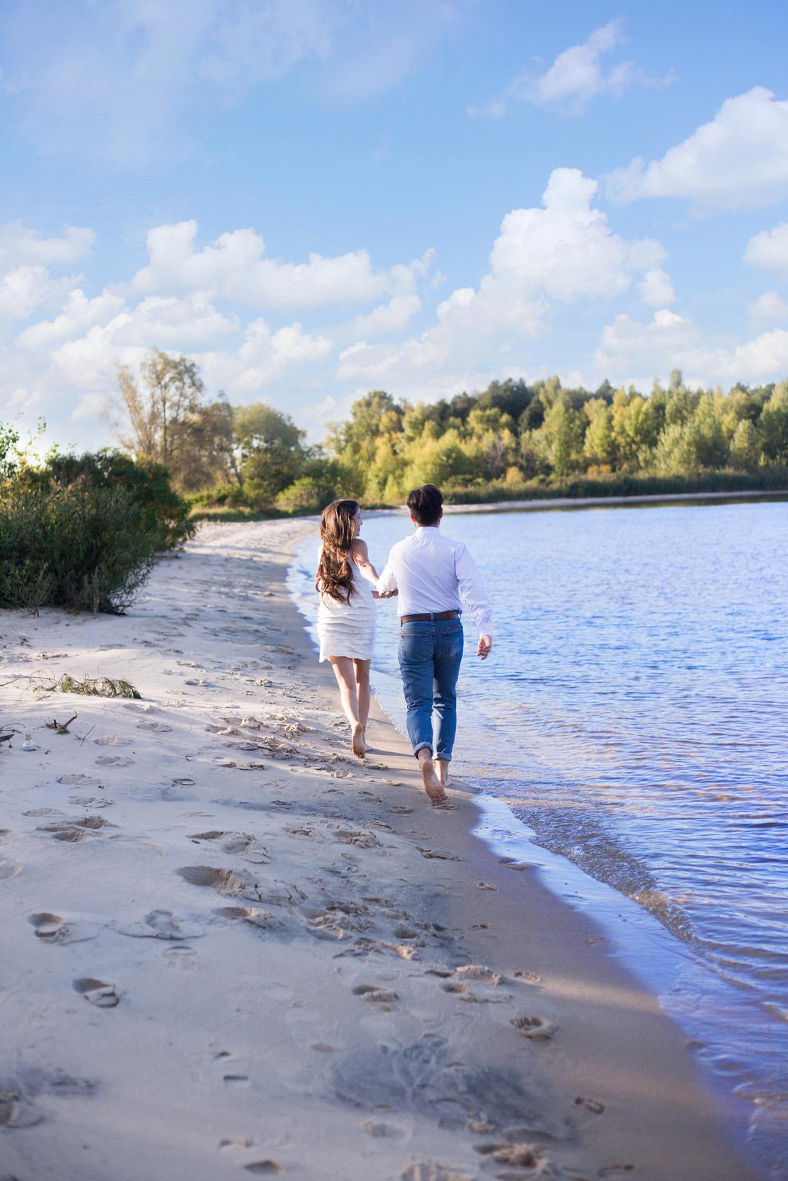 Бегут по пляжу, пара бежит по берегу моря, босеком по песку