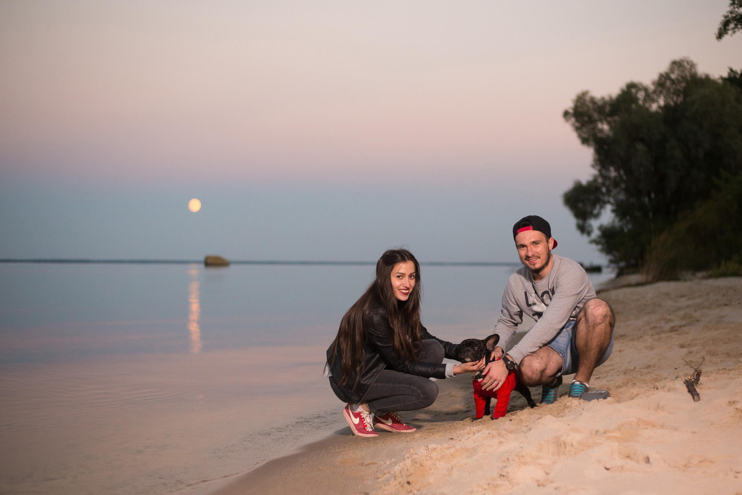 пара играет с собакой на берегу моря,на пляже с собакой