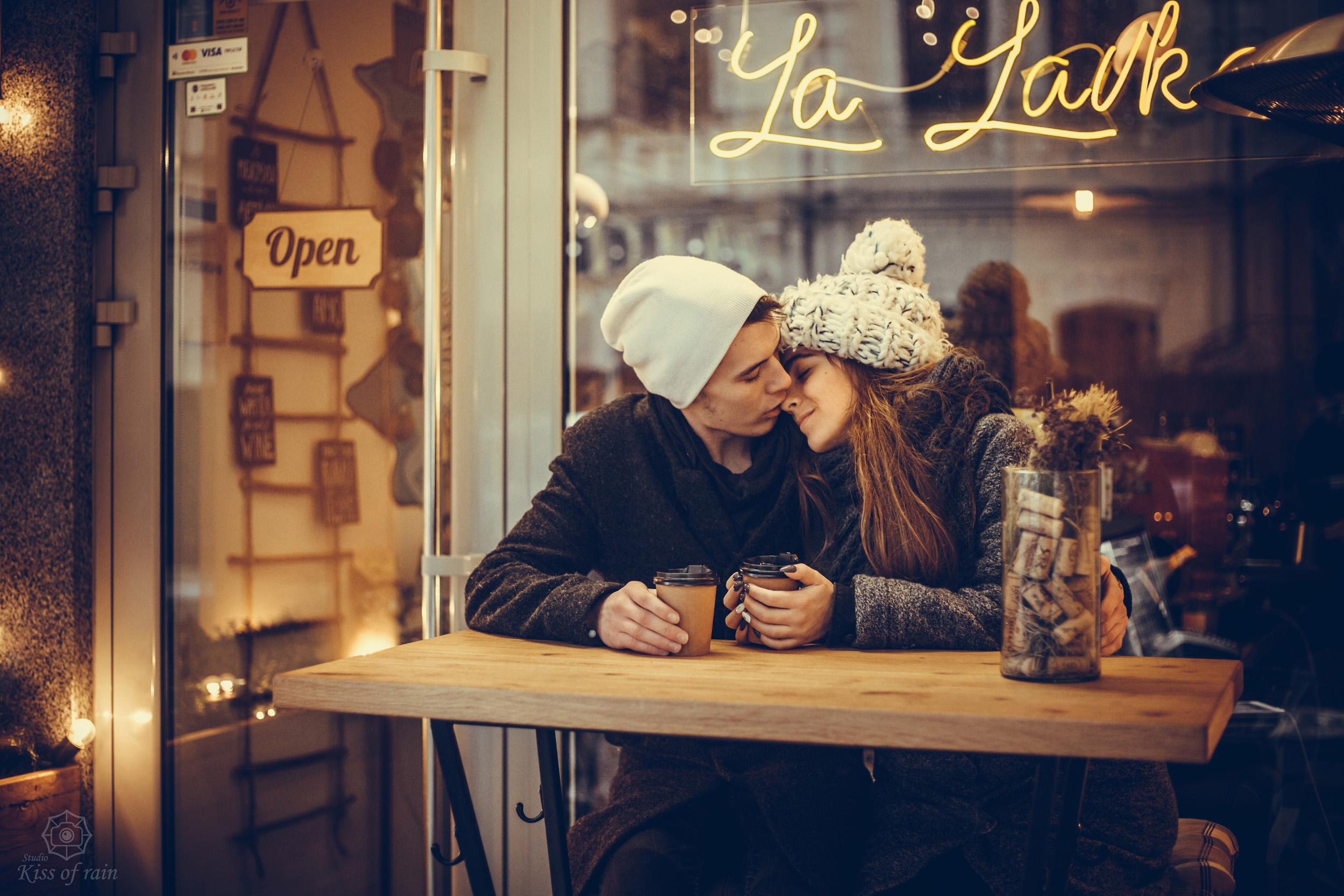 влюблённая парочка ночью фото, лавстори красивых молодых людей фото, влюблённая пара возле ветрины кафе фото, пара сидит за столиком возле кафе вечером
